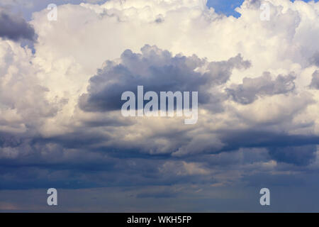 Thunderclouds float in the sky, gathering together and hide the blue sky. - Stock Photo