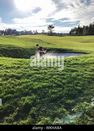 Man Playing Golf Against Sky - Stock Photo