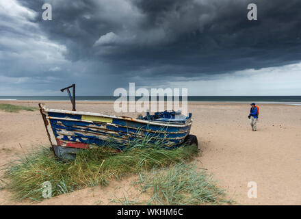 Female hiker walking on beach under a stormy sky at Marske between Redcar and Saltburn bt the seaon the north east coast of England. UK - Stock Photo