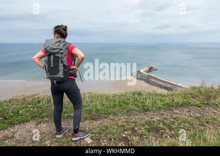 Mature female hiker on The Cleveland Way coastal trail overlooking Cattersty Sands beach at Skinningrove, North Yorkshire, England. UK - Stock Photo