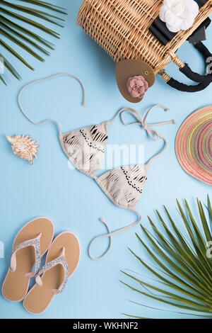 Summer background with palm leaves, fashion hat, bikini, flip flops, straw beach bag on a light pastel blue background, travel and vacations concept, - Stock Photo