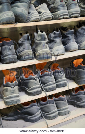 Many safety shoes in different sizes at a plant - Stock Photo