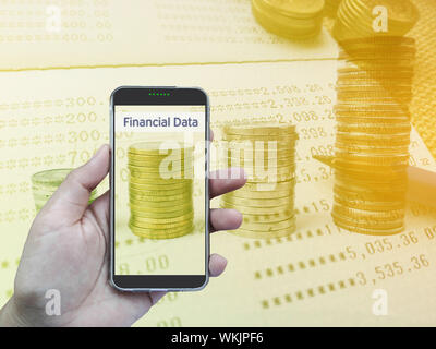 Digital Composite Image Of Hand Holding Mobile Phone Against Financial Figures - Stock Photo