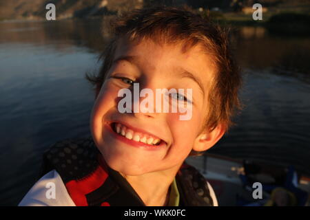 Portrait Of Happy Boy Smiling While Standing In Boat On River - Stock Photo