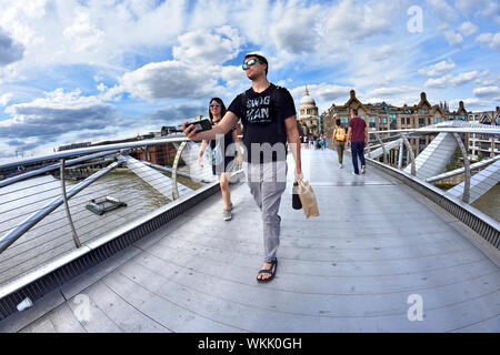London, England, UK. People crossing the Millennium Bridge on a sunny day in August - man taking a selfie or video - Stock Photo