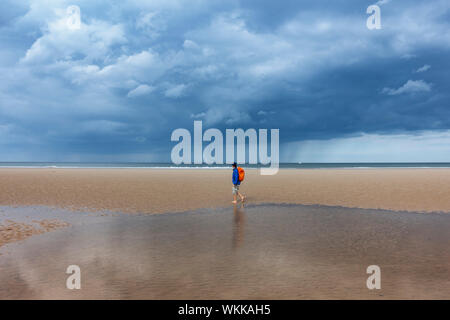 Female hiker walking on beach under a stormy sky at Saltburn on the Yorkshire coast. UK - Stock Photo