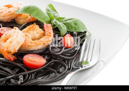 Black spaghetti with shrimps isolated on white - Stock Photo