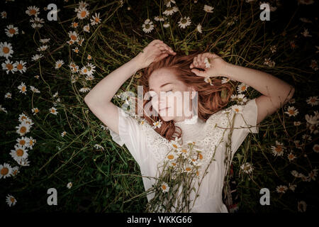 Beautiful woman enjoying daisy field, nice female lying down in meadow of flowers, pretty girl relaxing outdoor, having fun, holding plant, happy youn - Stock Photo