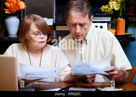 Senior couple at home organizing many bills - Stock Photo