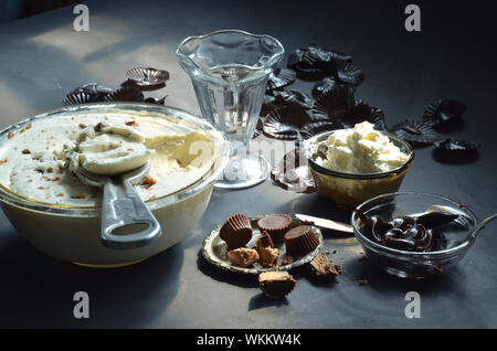 High Angle View Of Ice Cream In Bowls With Peanut Butter Cupcakes And Chocolates On Table - Stock Photo