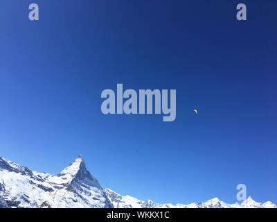 Low Angle View Of Paraglider Against Blue Sky - Stock Photo
