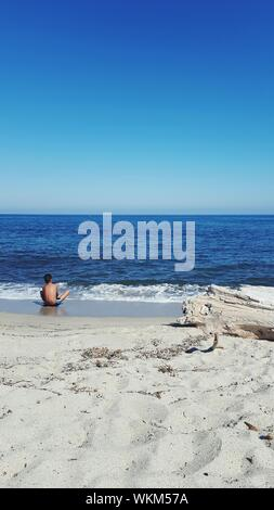 Rear View Of Shirtless Man Sitting On Shore At Beach Against Clear Blue Sky - Stock Photo