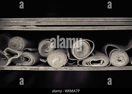 Close-up Of Rolled Up Fabrics In Shelf At Bakery - Stock Photo