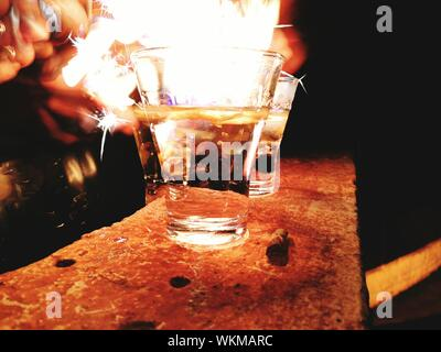 Cropped Hand Of Person Flaming Shot At Night - Stock Photo