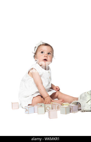 Girl playing with alphabet blocks isolated on a white background - Stock Photo