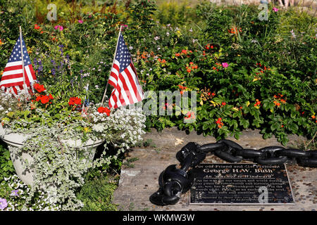 Memorial plaque for George H.W Bush and American flags by Bush Compound aka the Summer White House in the background.Kennebunkport.Maine.USA - Stock Photo