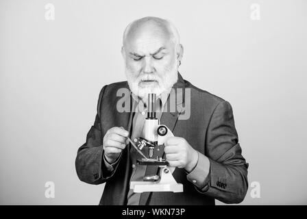 Mature man formal suit with microscope. Doctoral work and postdoctoral employment. Molecular biology PhD projects. Biology experienced lecturer. Professor university lecturer. Scientist microbiology. - Stock Photo