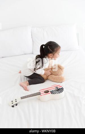 Asian little girl playing ukulele in bedroom - Stock Photo