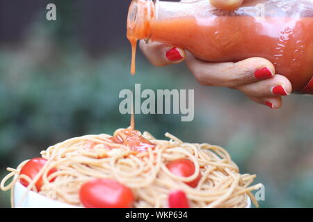 Cropped Hand Of Woman Pouring Sauce On Noodles Stock Photo