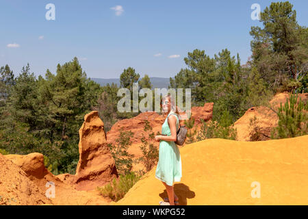 Young attractive blond caucasian woman, independent solo traveler in Ochre Trail in Roussillon, hiking path in Sentier des Ocres - Stock Photo