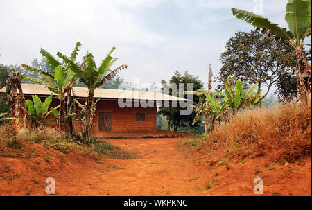 Typical African red clay or soil brick with tin roof house - Stock Photo