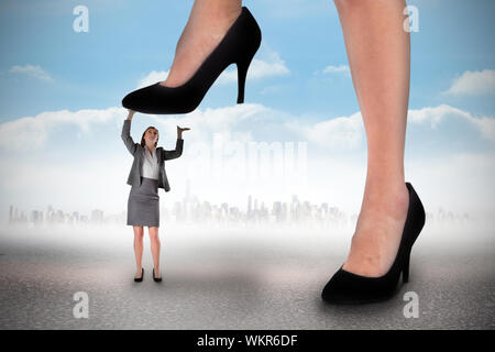 Composite image of businesswoman stepping on tiny businesswoman against cityscape on the horizon - Stock Photo