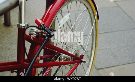 Close-up Of Bicycle Parked On Footpath - Stock Photo