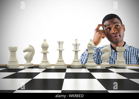 Composite image of thinking casual businessman with chessboard - Stock Photo