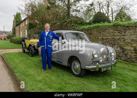 Car enthusiast, in made to measure blue overalls, poses in front of his vintage Austin saloon, Litchborough, UK - Stock Photo