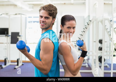 Fit couple exercising together with blue dumbbells at the gym - Stock Photo