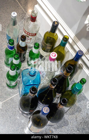 Empty alcohol bottles left after a party - Stock Photo