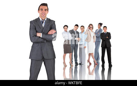Composite image of businessman in grey suit smiling at camera against group of business people - Stock Photo