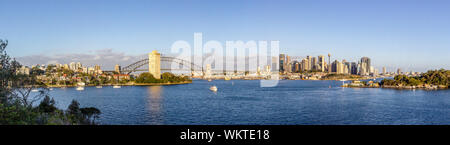 Sydney city landmarks panoramic view across Sydney Harbour along Harbour Bridge arch towards cityscape skyscrapers at sunrise