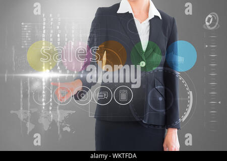 Businesswoman touching the word sales on interface against grey vignette - Stock Photo