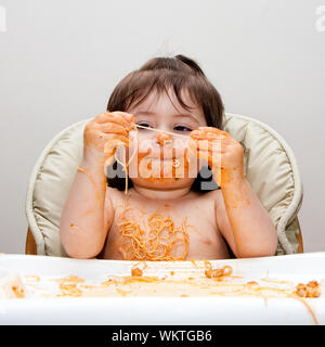 Happy baby having fun eating messy covered in Spaghetti holding Angel Hair Pasta red marinara tomato sauce. - Stock Photo