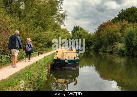 Couple walking away along the River Lea toe path near Narrowboats - Stock Photo