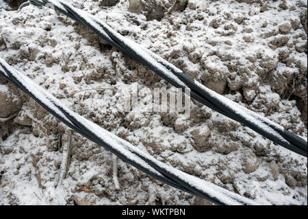 Laying a fiber optic and electricity cables in the frozen ground, buried cables for fast internet in rural region - underground cabling in Finland - Stock Photo