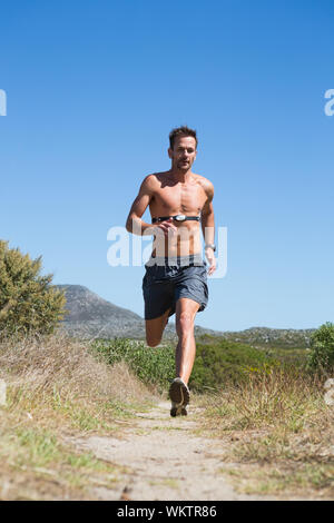 Shirtless man jogging with heart rate monitor around chest on a sunny day - Stock Photo