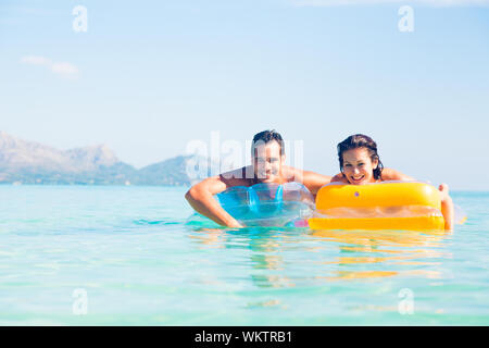 Portrait Of Young Couple Floating On Inflatable Rafts In Sea Against Sky - Stock Photo