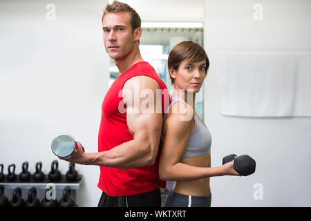 Fit couple lifting dumbbells together looking at camera at the gym - Stock Photo