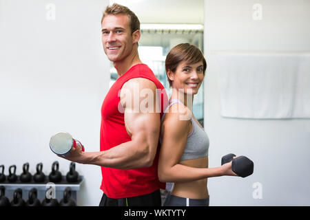 Fit couple lifting dumbbells together smiling at camera at the gym - Stock Photo