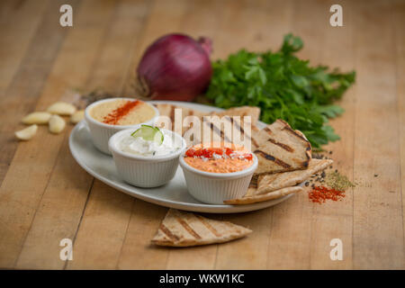 greek appetizers with olives and dips served on white plates with pita bread - Stock Photo