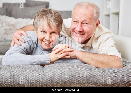Portrait Of Happy Couple Relaxing On Bed At Home - Stock Photo