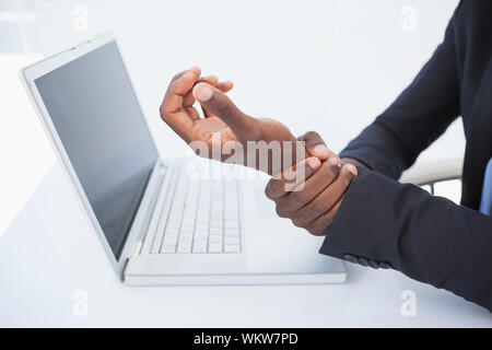 Businessman holding his sore wrist from typing in his office - Stock Photo