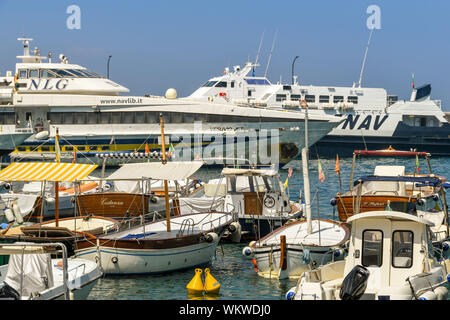 ISLE OF CAPRI, ITALY - AUGUST 2019: Small fishing boats and large fast ferries in the harbour on the Isle of Capri. - Stock Photo