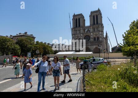 Paris, FRANCE - June 27, 2019: tourists still visiting the Cathdrale Notre-Dame de Paris under construction and refurbishment rebuild work ongoing - Stock Photo