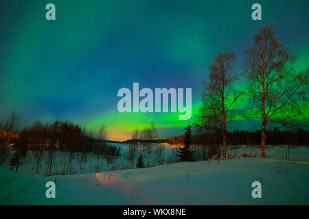 Intense northern lights - Aurora borealis over Lake in Finland - Stock Photo