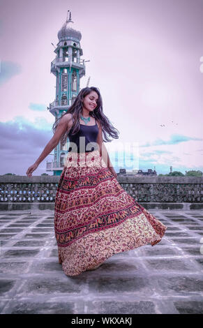 Happy Young Woman Dancing While Standing Against Sky - Stock Photo