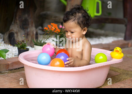 Shirtless Baby Boy Playing With Colorful Balls In Bathtub - Stock Photo