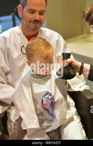Dad holds a little boy at the hairdresser for a first haircut - Stock Photo